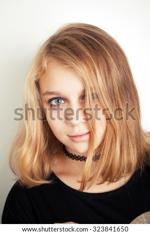 Beautiful Caucasian blond teenage girl in black. Studio portrait over white background with soft shadow