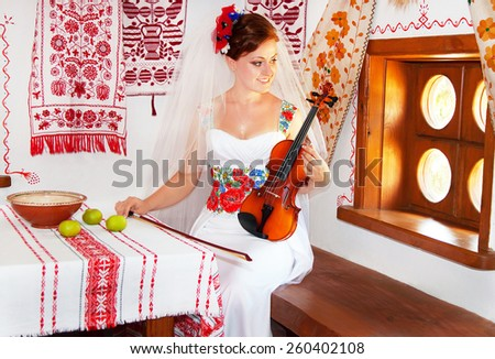 Beautiful caucasian bride in the dress and the bridal veil in the ukrainian style is holding the violin. Happy smiling girl with fiddle in the ukrainian traditional house. Ukraine. Wedding concept.