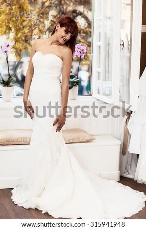 Beautiful Caucasian bride wearing wedding, looking over her shoulder - stock photo
