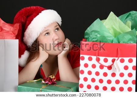 Beautiful caucasian brunette looking inside her christmas gift bag  - stock photo