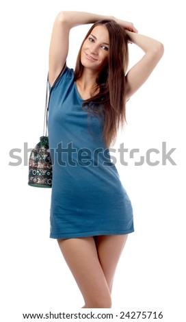 beautiful caucasian brunette model in blue dress with bag poses on white