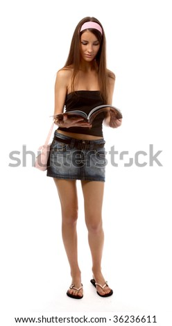 beautiful caucasian brunette model in jeans skirt walks and reads magazine - stock photo