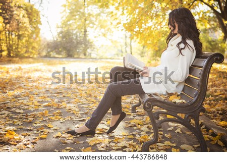 Beautiful caucasian brunette young woman in warm autumn day at park. Yellow leaves and sunshine. Fall season. Woman in white sweater, a book in her hands, reading on a bench, smiling. Copy space - stock photo