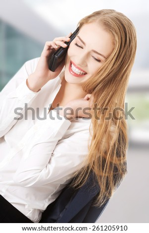 Beautiful caucasian business woman is talking through phone.