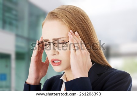 Beautiful caucasian business woman with headache - stock photo
