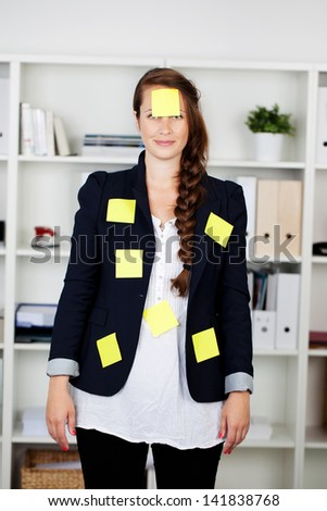Beautiful caucasian businesswoman standing in the office with post it notes on her body - stock photo