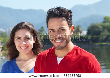Beautiful caucasian couple in vacation looking at camera - stock photo