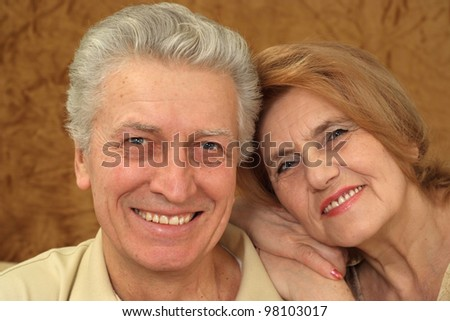 Beautiful Caucasian couple of aged people sitting on a brown background