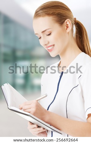 Beautiful caucasian doctor or nurse is writing in notebook - stock photo