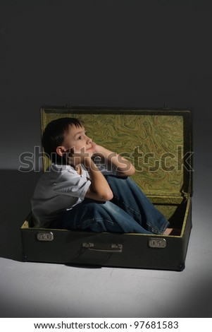 Beautiful Caucasian dream boy sitting in the suitcase on dark background