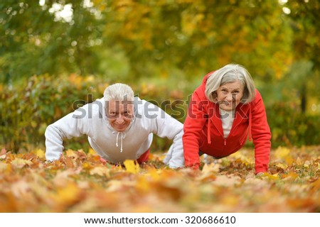 Beautiful caucasian elderly couple trainig in the park in autumn