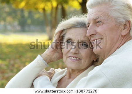 beautiful caucasian elderly couple walking in the park in autumn - stock photo