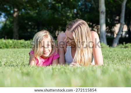 Beautiful Caucasian ethnicity mother and daughter bonding at park - stock photo