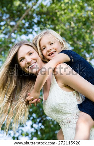 Beautiful Caucasian ethnicity mother and daughter having fun and bonding at park - stock photo