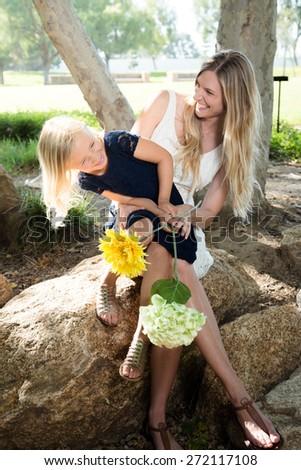 Beautiful Caucasian ethnicity mother and daughter having fun at park - stock photo