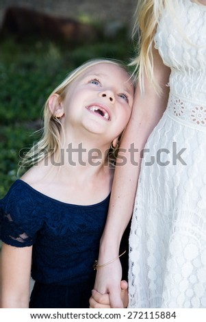Beautiful Caucasian ethnicity mother and daughter holding hands and bonding at park - stock photo