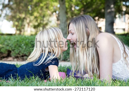 Beautiful Caucasian ethnicity mother and daughter lying on grass and having fun at park - stock photo