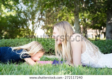 Beautiful Caucasian ethnicity mother and daughter lying on grass and laughing at park - stock photo