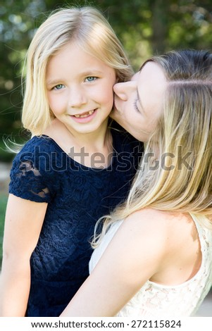 Beautiful Caucasian ethnicity mother kissing her daughter - stock photo