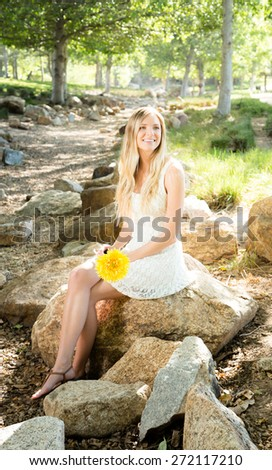 Beautiful Caucasian ethnicity woman in a white dress at park - stock photo