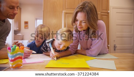 Beautiful caucasian family drawing for her young child. - stock photo