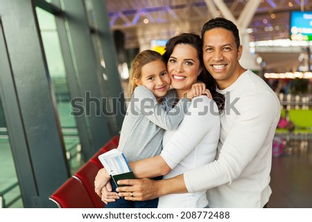 beautiful caucasian family looking at the camera at airport - stock photo