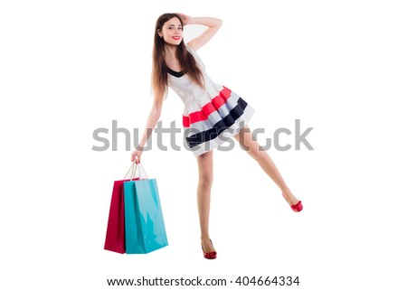 beautiful caucasian female in dress with shopping bags. Studio shot on white background - stock photo