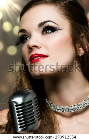 Beautiful caucasian female singer. The girl is holding a retro performance microphone and wearing a black evening dress with a diamond choker necklace and glamor make-up. - stock photo