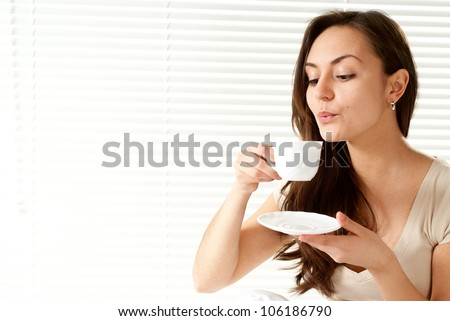 Beautiful Caucasian female sitting on a bed with a cup on a light background - stock photo