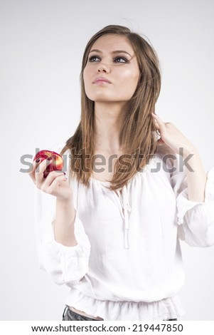 Beautiful caucasian girl holding a red apple, wearing a white blouse with light grey background  - stock photo