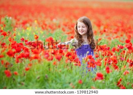 Beautiful Caucasian girl playing in red flower field - stock photo
