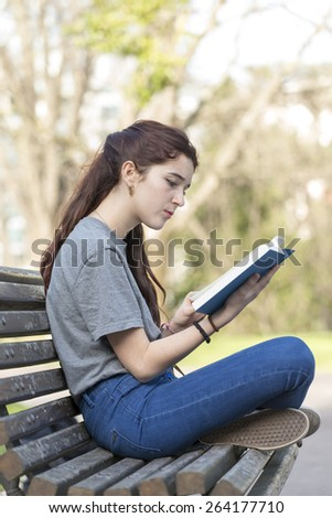 Beautiful caucasian girl sitting on old wood bench in the park and reading blue book. - stock photo