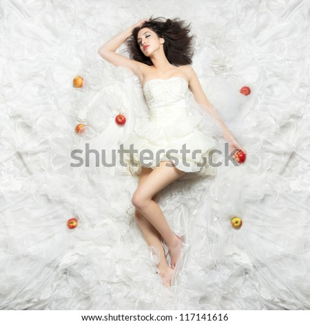 Beautiful Caucasian girl sleeping after eating the forbidden fruit. Photographed from above