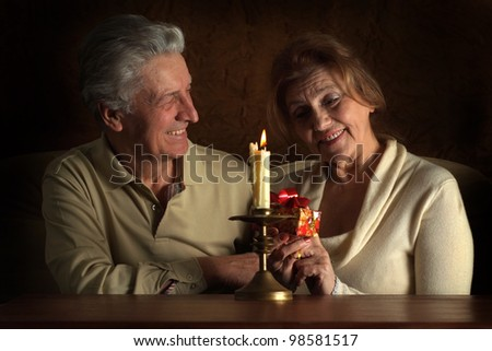 Beautiful Caucasian joy couple of old people sitting on a brown background