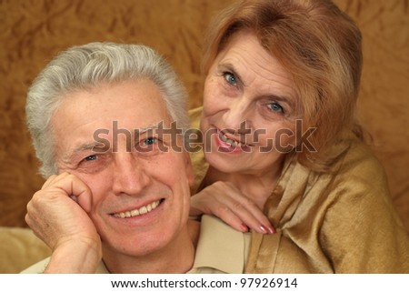 Beautiful Caucasian luck couple of aged people sitting on a brown background