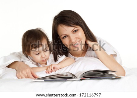 Beautiful caucasian mama and daughter is lying on the bed with a book