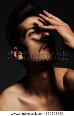 beautiful caucasian man with hand covering face