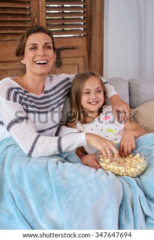 Beautiful Caucasian mother and child kid spending quality time sitting on sofa at their home eating popcorn and watching tv snuggling under blanket