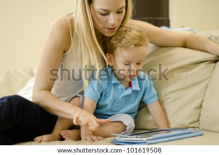Beautiful caucasian mother playing with her son and a tablet