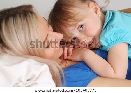Beautiful caucasian mum and daughter lying on the bed