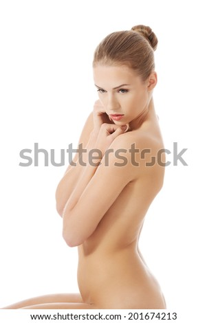 Beautiful caucasian naked woman sitting, side view. Isolated on white.