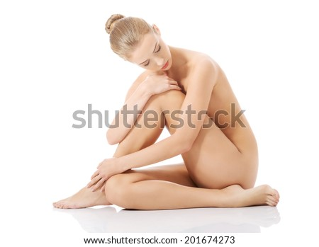 Beautiful caucasian naked woman sitting with fresh clean skin. Isolated on white.