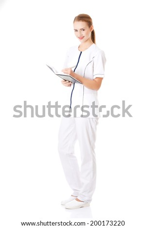 Beautiful caucasian nurse or doctor is writing in a notebook. Isolated on white. - stock photo