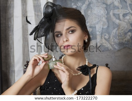 Beautiful Caucasian Pin Up Girl with a perfume bottle  - stock photo