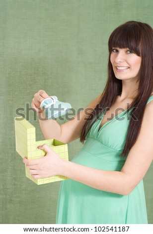 Beautiful Caucasian pregnant girl standing with bootees on white background