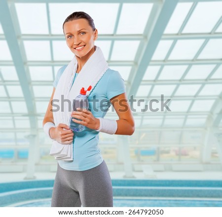 beautiful caucasian sportswoman standing on background of big wall window wearing sports clothes with white cotton towel holding opened bottle of water smiling and looking at camera  - stock photo