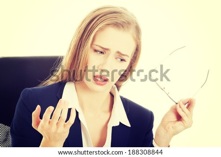 Beautiful caucasian surprised business woman is taking off her eyeglasses. Isolated on white. - stock photo