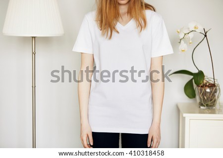 Beautiful Caucasian teenage girl, cropped portrait. Young attractive woman with loose red hair wearing blank white T-shirt and black skinny jeans while standing against home interior background - stock photo