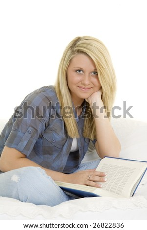 Beautiful Caucasian teenager setting in bed reading a book