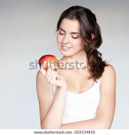 beautiful caucasian thoughtful young woman  in white singlet holding red apple over gray background - stock photo